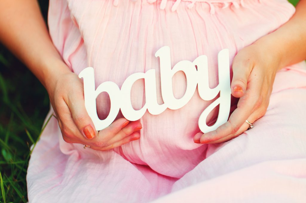 "Label ""Baby"" in the hands of a pregnant woman outdoors"